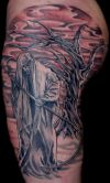 grim reaper and tree tattoo on hip